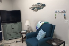 fishes on the wall between recliner chair and tv with streaming video